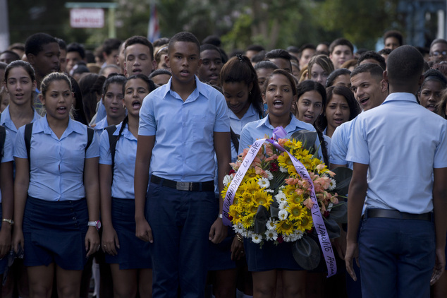 Students march, one carrying a wreath, to a memorial honoring the late Fidel Castro, in the Ciudad Escolar Libertad neighborhood in Havana, Cuba, Monday, Nov...