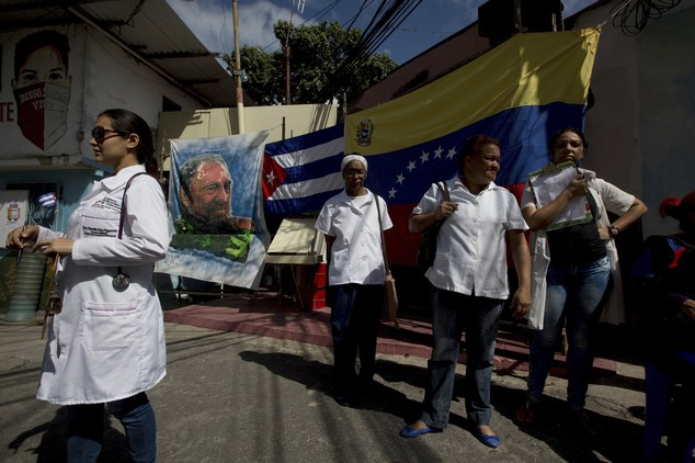 Cuban doctors working in Venezuela wait for pacients outside their clinic, where an image of Fidel Castro and a Cuban and Venezuelan flag hangs, in the 23 de...