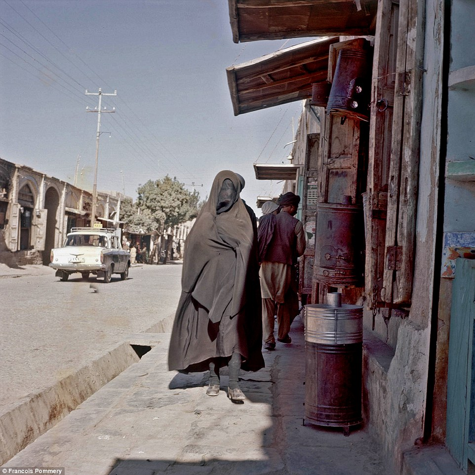 A woman in a burka walks pasty rickety buildings in Herat in 1974