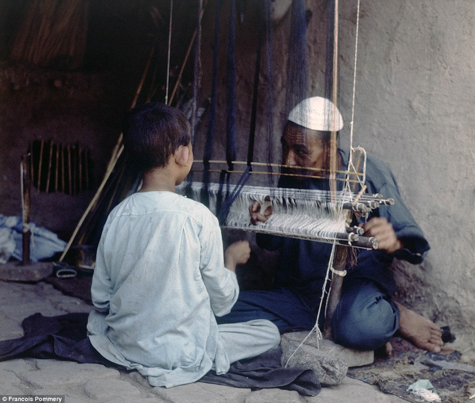 Passing knowledge from generation to generation: A man shows a young boy how to use his weaving loom