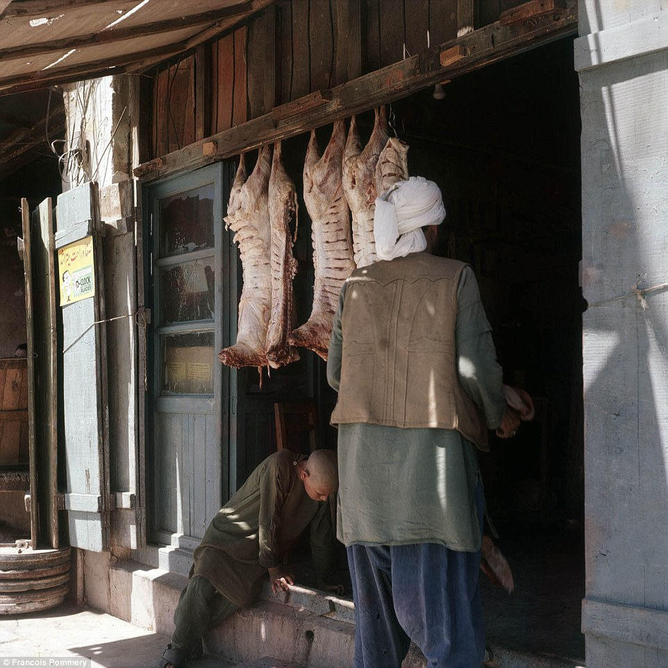 Meat hangs up in a butcher's shop in Herat, watched over by a man and a young boy