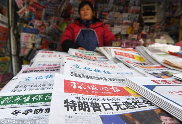 A newsstand vendor stands behind newspapers, including one with a  story (foreground) about Donald Trump that reads: 'Trump's inability to keep his mouth shut is stunning'