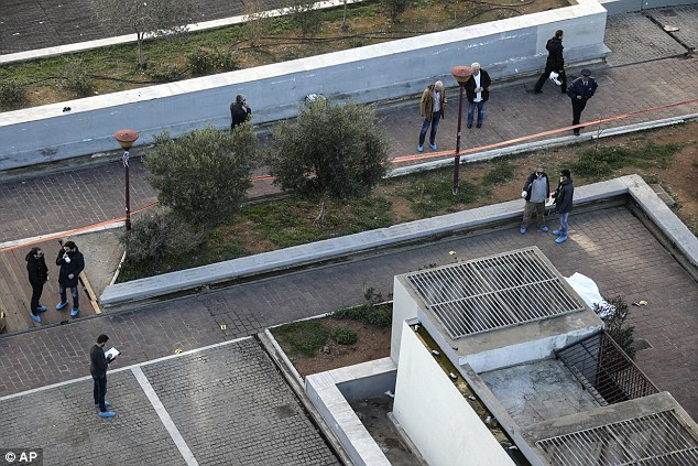 Pictured: Detectives takes notes as they inspect the scene of the shooting  in central Athens