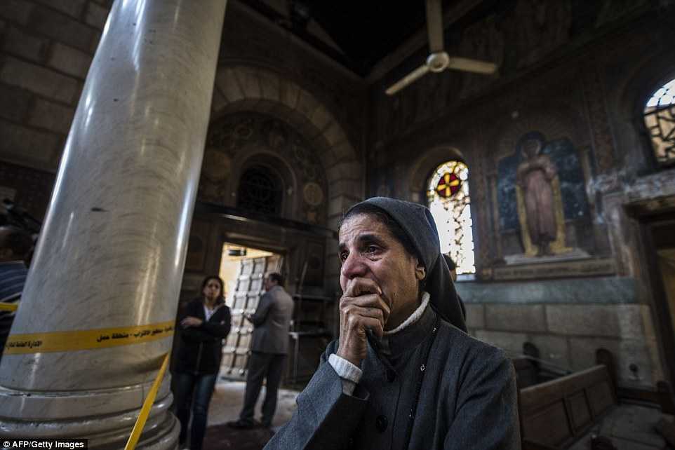 A nun inside the cathedral looked shellshocked, pictured, and could not hold back her tears after the deadly attack
