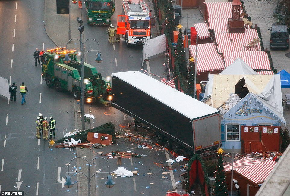 Carnage: The lorry used to kill a dozen people in Berlin last night was towed away from the scene as a 23-year-old asylum seeker was being interrogated