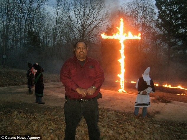 Daryl Davis stands at a burning of the cross ceremony with KKK members in the background. The burning is synonymous with the group who do it as mark their religion and for intimidatory purposes