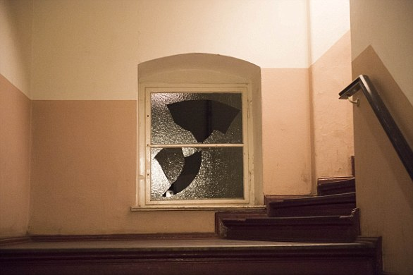 A window in the hall outside the mosque, which was covered with graffiti and dirt, had been smashed