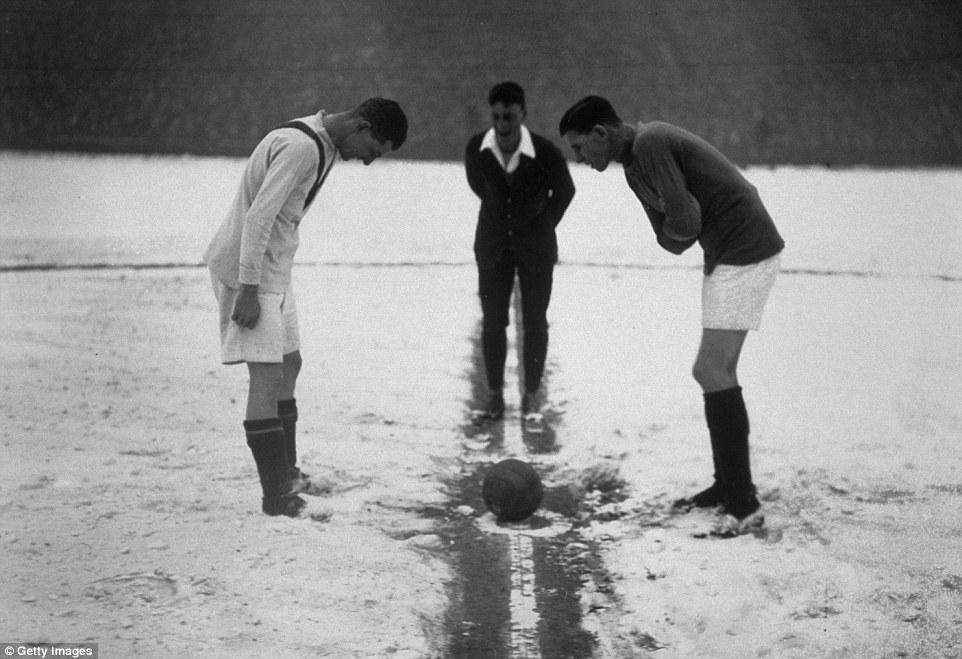 The referee tosses up on a snow-covered pitch at the start of a match between Arsenal and Manchester United at Highbury