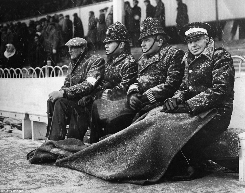 Policemen and ambulancemen try to stay warm on the touchline at White Hart Lane football ground during a blizzard