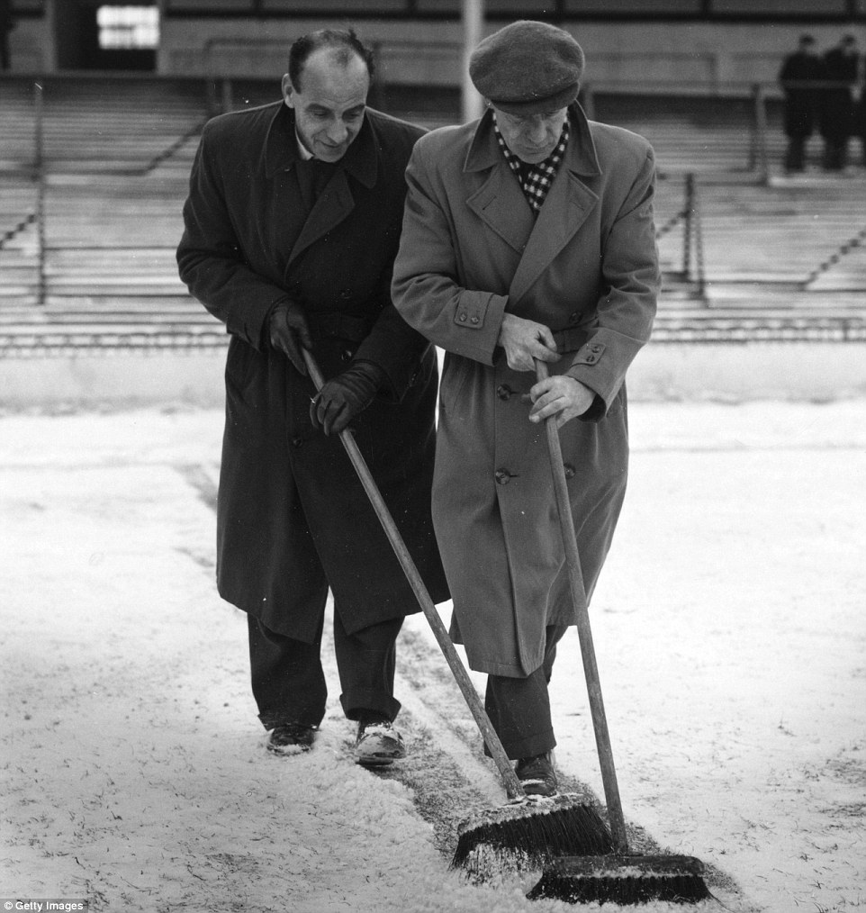 Tottenham's ground staff sweep snow from the goal line before the match between Tottenham and Birmingham City