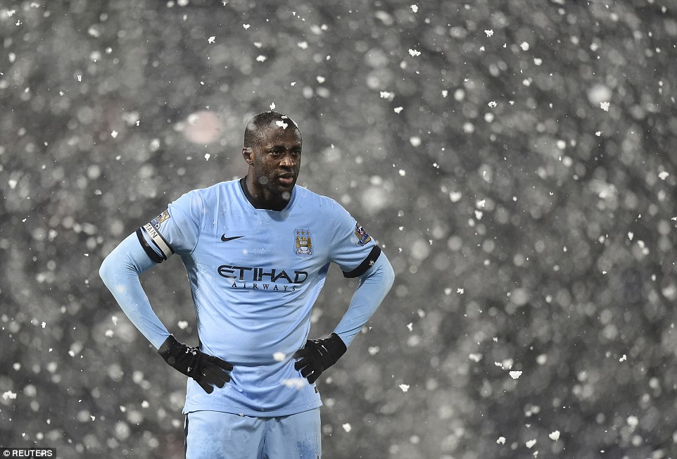 Manchester City's Yaya Toure stands in the snow during a Premier League match between Manchester City and West Brom