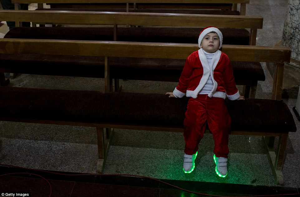 A young boy dressed in a santa outfit waits for the start of Christmas Day mass at Mar Hanna church near Mosul, Iraq