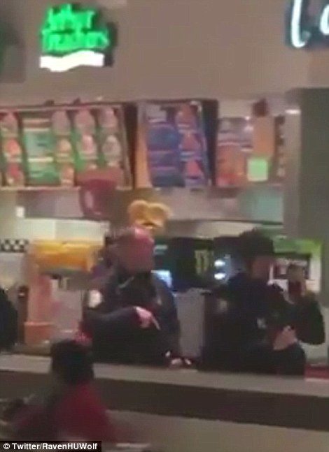 Mall cops: Heavily armed police (left) were deployed at The Mills in Jersey Gardens after the sound of a chair thrown in a brawl was misidentified as a gunshot