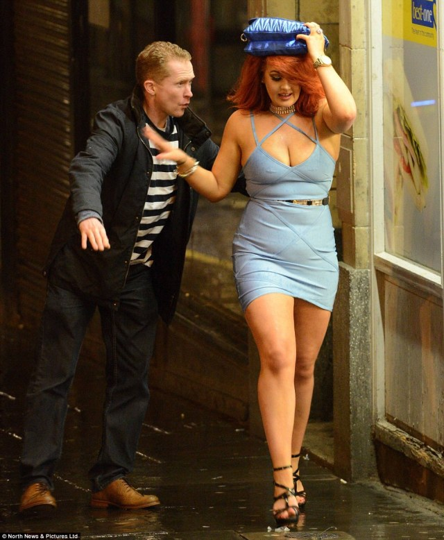 A woman wards off the advances of a man, while trying to protect her hair from the rain in Newcastle