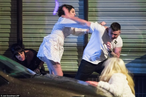 A tattooed man in a white T shirt bats off a woman in King Street, in Manchester, as the celebrations turned violent