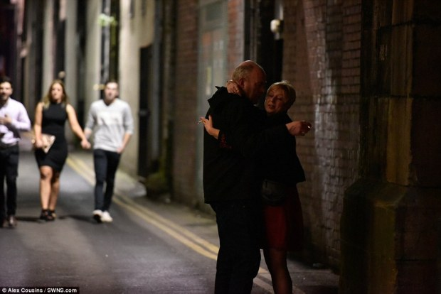 A couple cuddle in Leeds as a younger group make their way down the road as Britons ushered in 2017