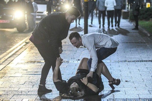 A woman is helped to her feet by two male friends after crashing to the ground during the New Year party in Birmingham