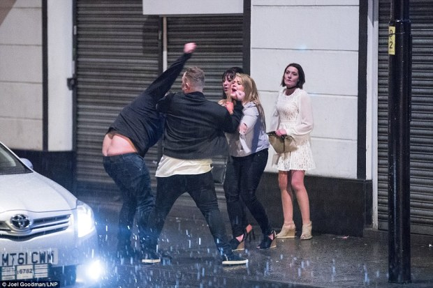 Two men come to blows in the heavy rain in Manchester as a distressed woman tries to break them apart