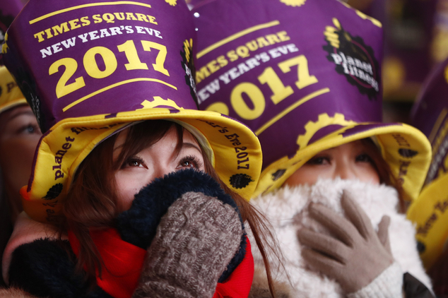 Revelers bundle up while gathered at Times Square during a New Year's Eve celebration Saturday, Dec. 31, 2016, in New York. (AP Photo/Julio Cortez)