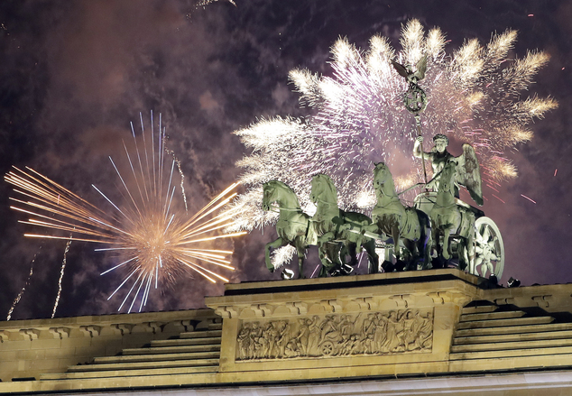 Fireworks light the sky above the Quadriga at the Brandenburg Gate shortly after midnight in Berlin, Germany, Sunday, Jan. 1, 2017. Hundred thousands of peop...