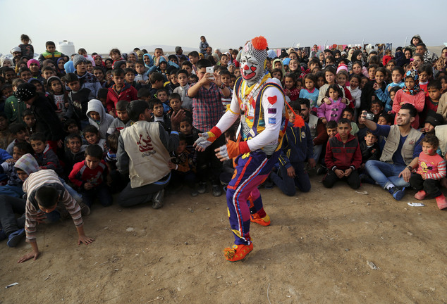 A clown performs during a New Year's celebration for internally displaced children at the Hassan Sham camp, east of Mosul, Iraq, Saturday, Dec 31, 2016. (AP ...
