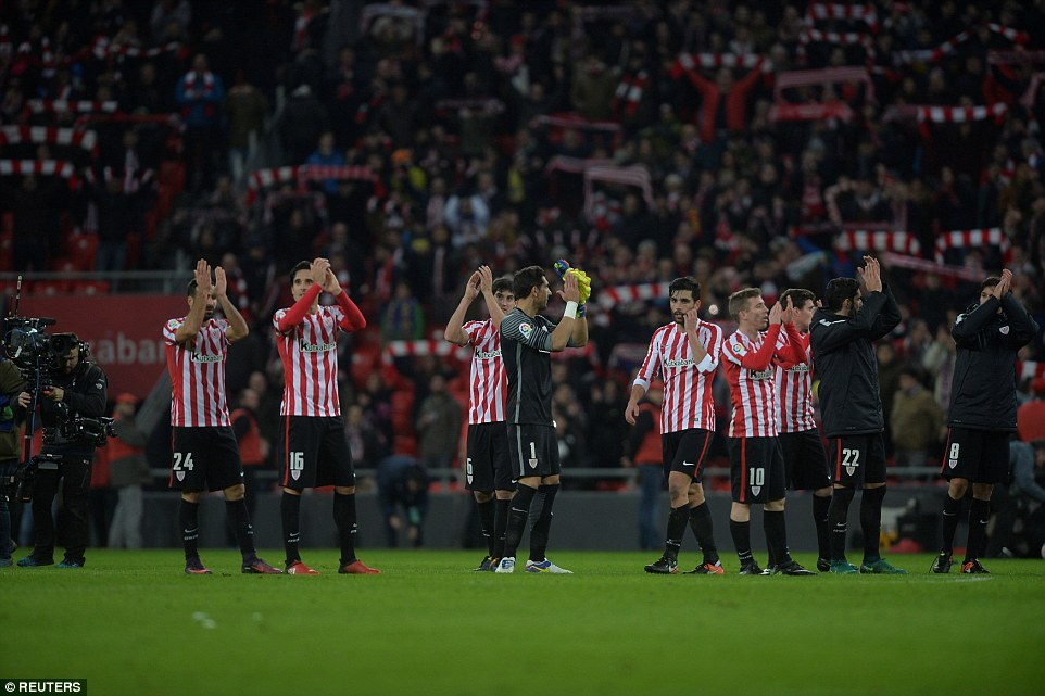 Athletic Bilbao players are followed by the television cameras as they take the applause of the crowd after full time