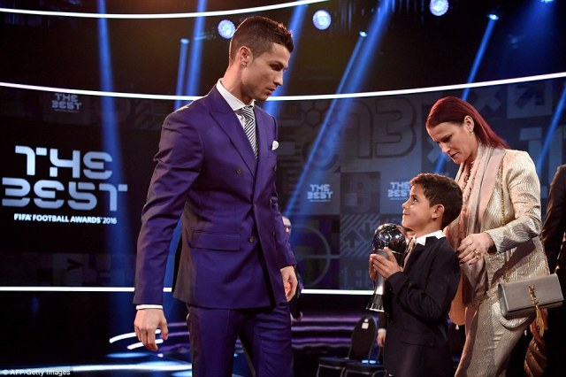 The forward's son,Cristiano Ronaldo Jnr, pulls a cheeky face while holding the trophy as the footballer's sister Elma looks on