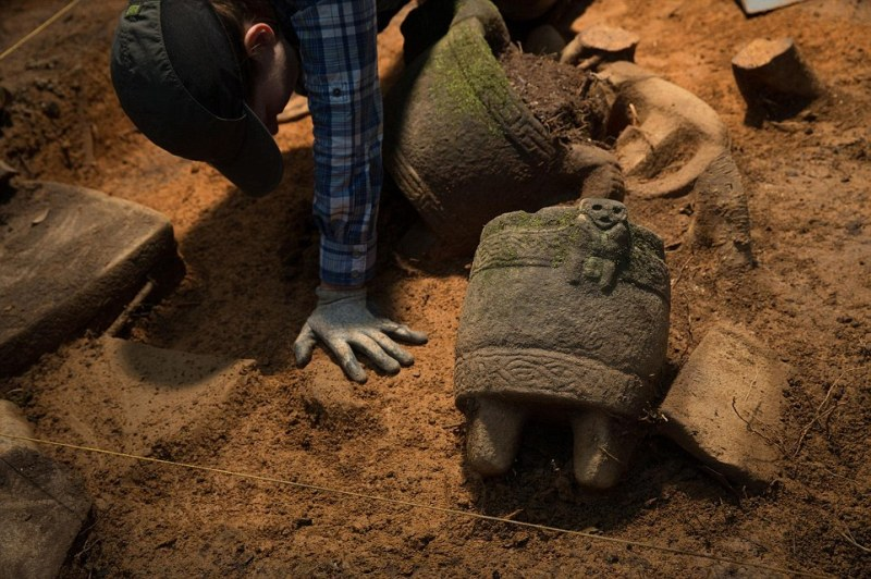 Excavation:Archaeologist Anna Cohen excavates stone vessels, one of which has a figure of unknown origin. Theories include the possibility that is acorpse bound for burial, a captive waiting sacrifice, or a half-monkey-half-human deity