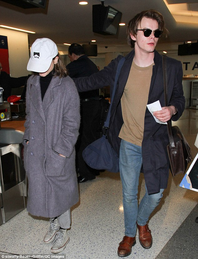 New couple? Stranger Things' Charlie Heaton protectively wrapped his arm around his co-star Natalia Dyer while catching a flight out of Los Angeles together on Monday
