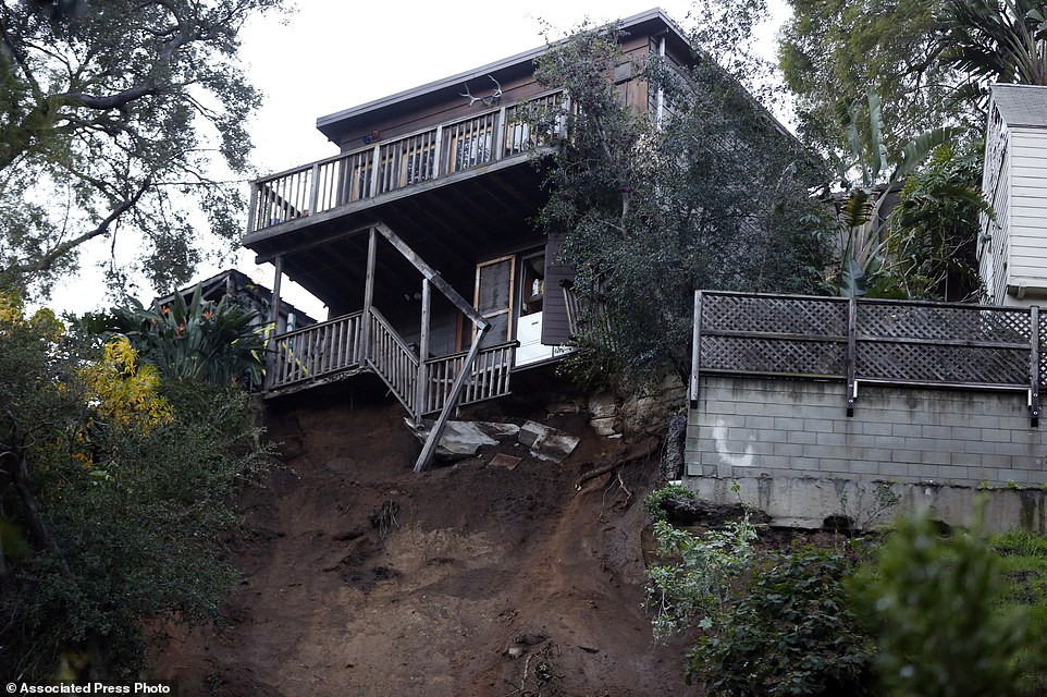 A home sits on the edge of a hill after a slab of concrete slid down a rain-soaked hillside in Los Angeles' Hollywood Hills neighborhood. The Los Angeles Fire Department says the chunk of foundation and retaining wall detached from a home and ended up on a street