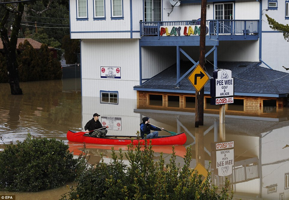 Residents paddle their canoe in front of the Pee Wee Golf and Arcade on Drake Road in Guerneville, California