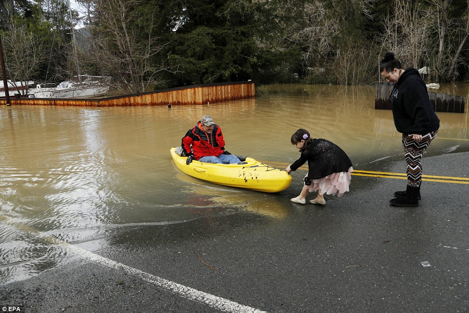 Some homes had mudlines about five feet high, marking how far the water rose. The water by that time was receding but still waist-deep in places. A young girl helps her father out of his kayak on Drake Road in Guerneville, California