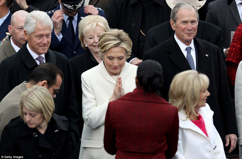 Former Democratic presidential nominee Hillary Clinton greets Michelle Obama as former President Bill Clinton and former President George W. Bush look on at the West Front of the U.S. Capitol on January 20, 2017 in Washington, DC. In today's inauguration ceremony Donald J. Trump becomes the 45th president of the United States