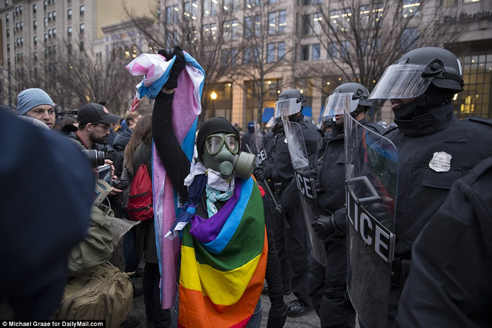 A rioter wrapped in a rainbow flag walks very close to the police line as protests turned violent in Washington
