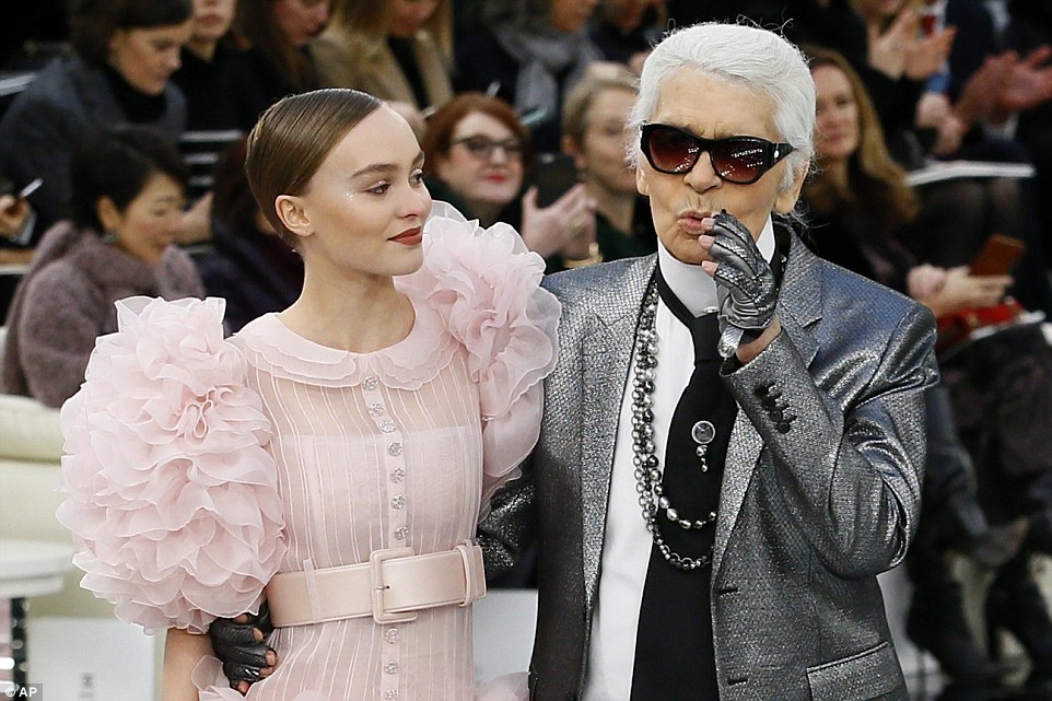 Homem principal: Lagerfeld jazzed acima de seu olhar monocromático usual com uma indicação jaqueta de prata e uma corda das pérolas