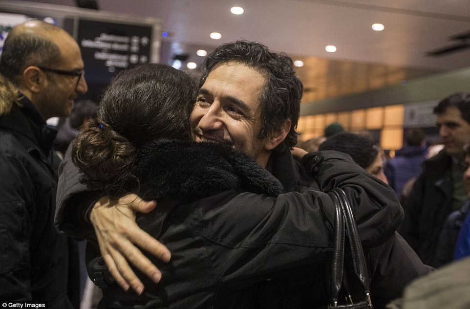 Mazdak Tootkaboni is pictured being embraced during a demonstration at Logan International Airport in Boston, Massachusetts. Tootkaboni is a US green card holder from Iran and a professor at the University of Massachusetts at Dartmouth, but he was still separated from other passengers and questioned