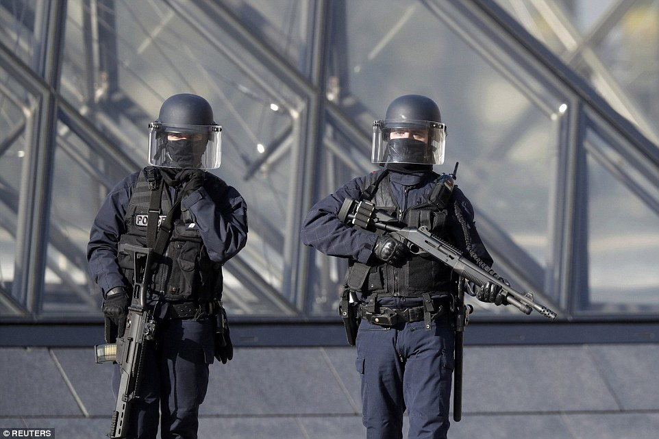 Armed officers stand guard in the courtyard outside the Louvre following this morning's attack, which has been described as 'terrorist in nature' by French Prime Minister Bernard Cazeneuve