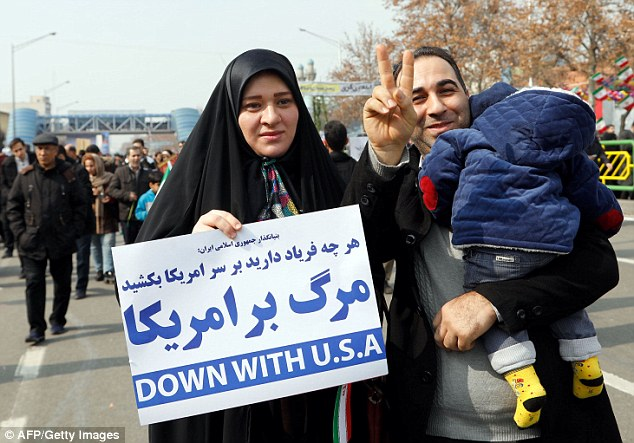 A woman holds a sign proclaiming opposition to the United States at today's rally