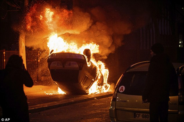 At least one car has been set on fire, pictured, by the group of demonstrators
