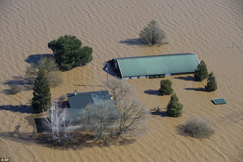 Water from the Cosumnes and Mokelumne rivers floods a house and barn north of Twin Cities Road east of Interstate 5 on Saturday in Elk Grove, California