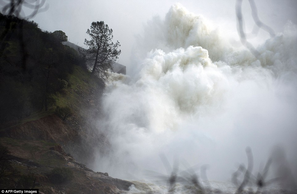 Raging: The water level dropped Monday behind the dam, reducing the risk of a catastrophic spillway collapse and easing fears that prompted the evacuation of nearly 200,000 people downstream