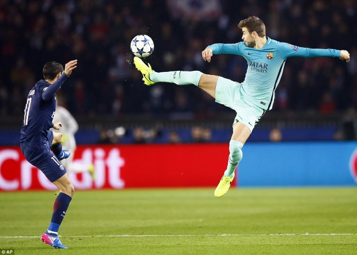Barcelona defender Gerard Pique flings out a right foot to try and bring the ball down under pressure from Angel Di Maria