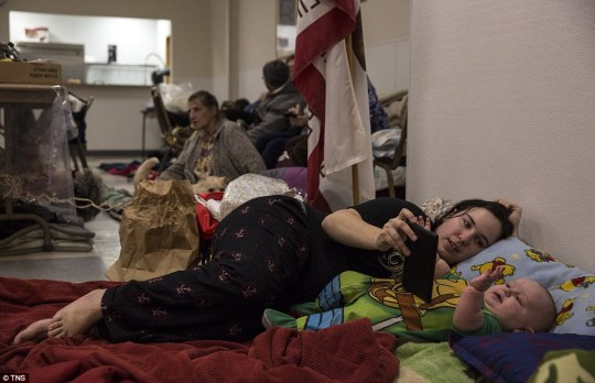 A woman entertains her baby in Bangor Community Hall as they wait with other evacuees for news about their homes