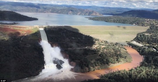 Water was allowed to flow back down the main waterway on Friday, February 10 (above) as levels in the reservoir continued to rise. By Sunday, it began eroding the emergency spillway the left of the dam and threatened to hop over the dam entirely and pour down into the towns at its foot