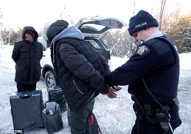 Dozens of refugees have been crossing from America into Canada over concerns about Trump's travel ban and stricter immigration policies. Above, a family from Yemen are taken into custody by the Royal Canadian Mounted Police after walking across the border into Hemmingford, Quebec on Tuesday