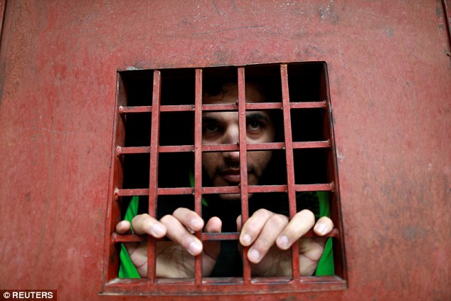 Behind the door of his cell, where he claims to spend all day reading the Koran to become a better person