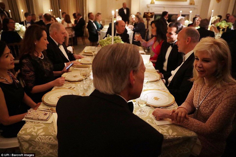 Texas Governor Greg Abbott (back to camera), Maryland Governor Larry Hogan and other sit together during the annual Governors Dinner in the East Room of the White House