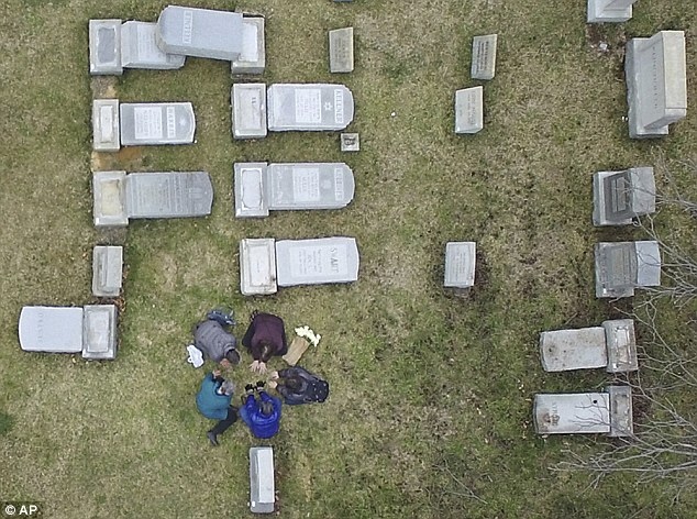 Other centers targeted included those in Cherry Hill, NJ; Providence, RI; Asheville, NC; Mobile, AL; Harrisburg, PA; Ann Arbor, MI; Talleyville, DE and Indianapolis, IN. Pictured: People in prayer at a Philadelphia cemetery that was vandalized