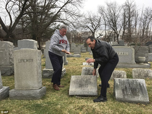 Police said  that about 100 headstones had been toppled at Mount Carmel Cemetary in Philadelphia. Pictured: Philly Mayor Jim Kenney, left, and David Pearl Jr lifting headstone of Pearl's grandfather which was damaged in the vandalism