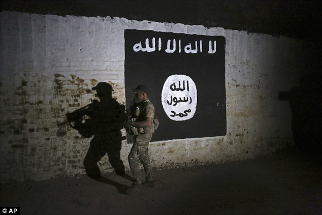 An Iraqi soldier inspects a recently-discovered train tunnel, adorned with an Islamic State group flag